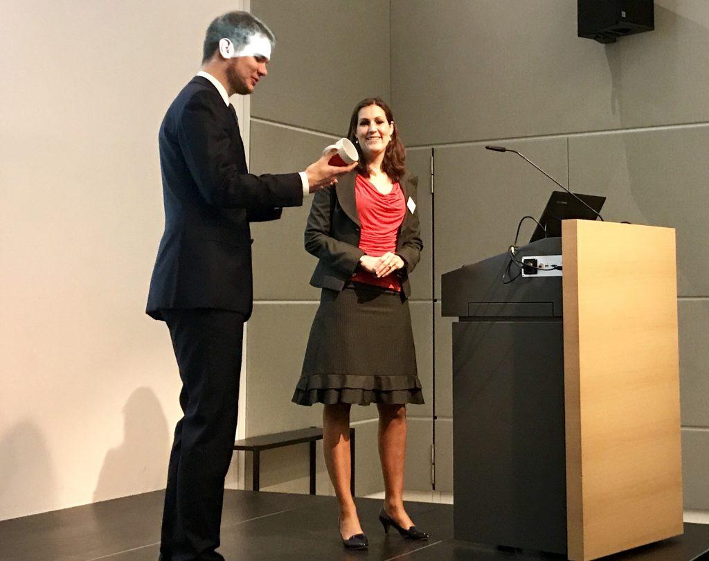 Dr. Vanessa Farmand, Leiterin der Kartellrechtsabteilung der REWE Group, erhält eine HHU-Tasse als Dank für ihren Vortrag